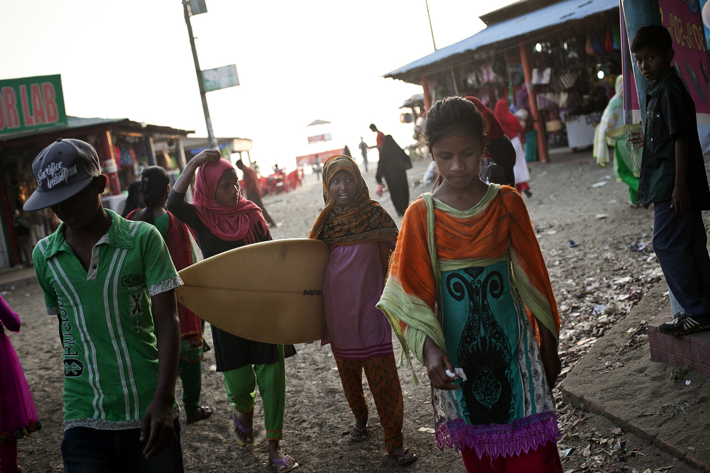 The girls walk through the marketplace near the beach after surfing
