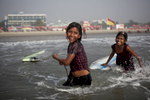 Aisha and Johanara laugh while surfing