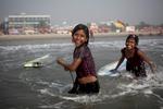 Aisha and Johanara laugh while surfing