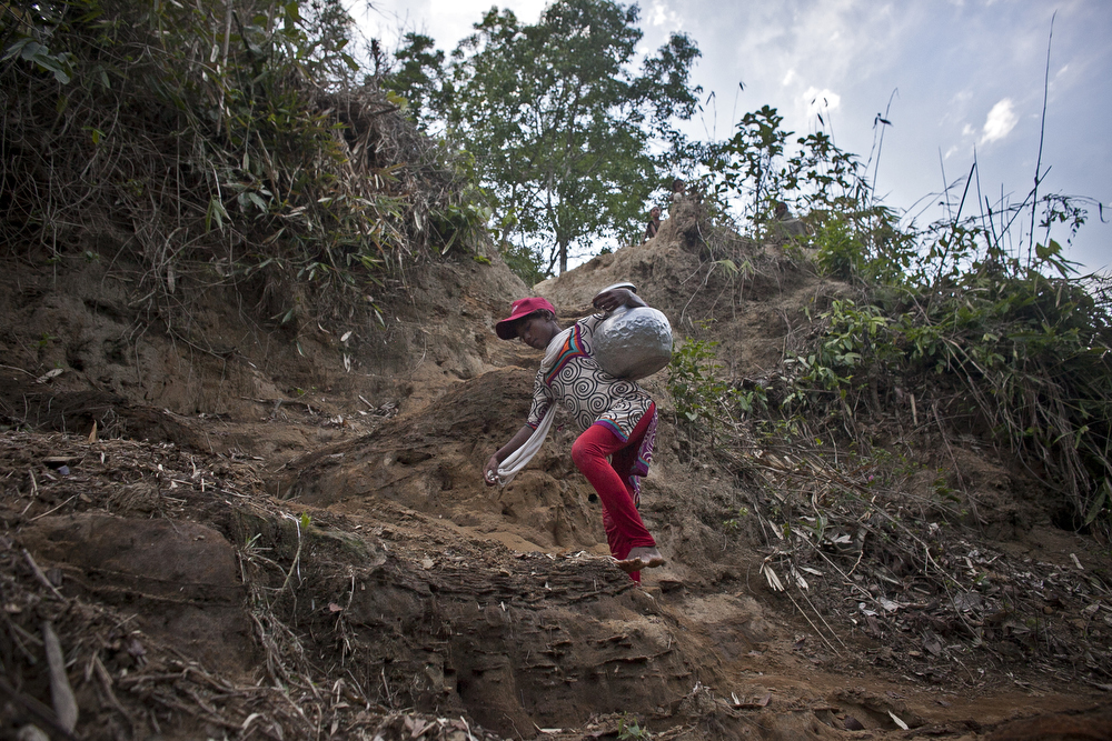 Rife climbs a steep hill after collecting water that her family will use for bathing, cooking, washing and drinking from her village's only water source