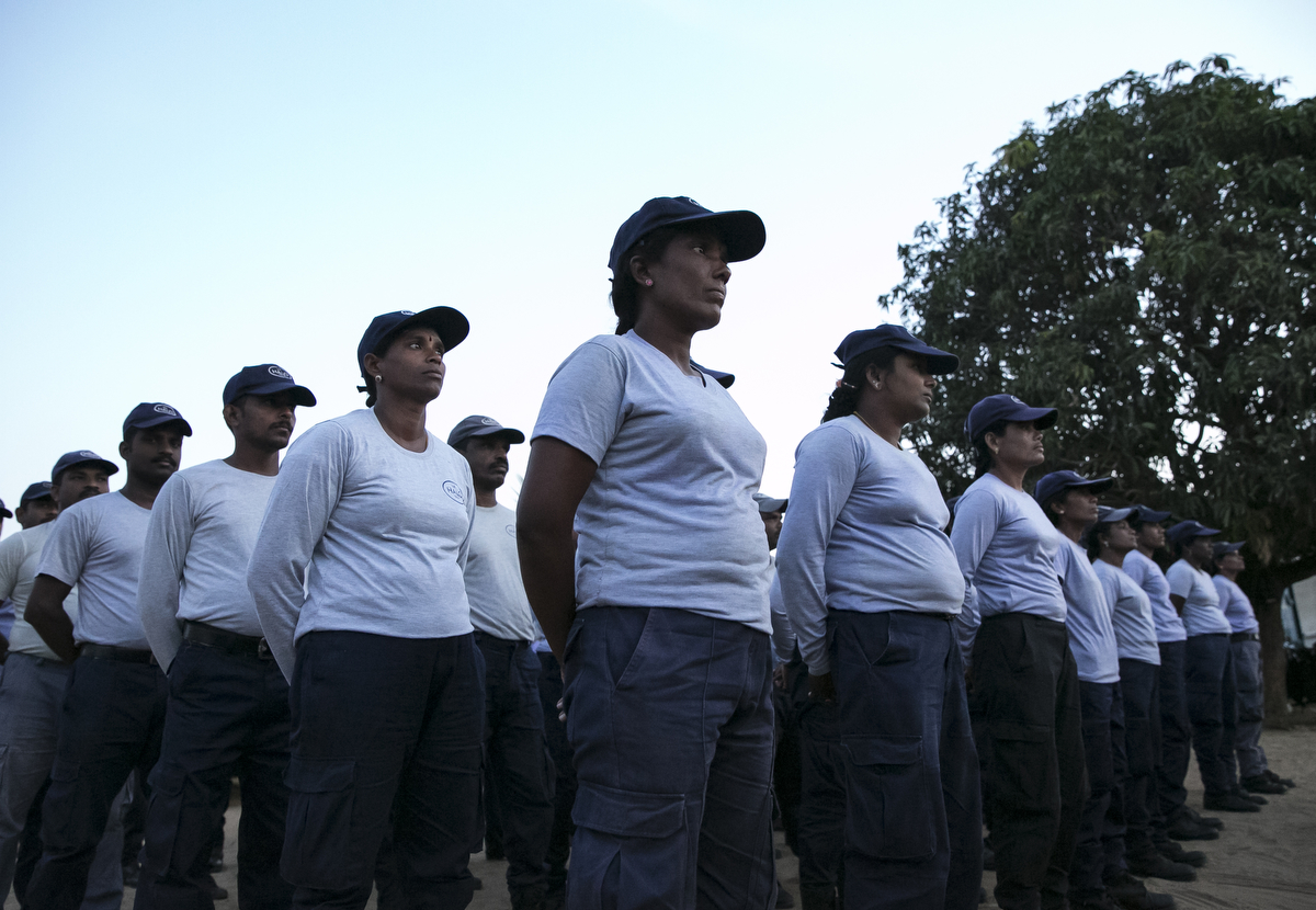 Female de-miners attend roll call before going to clear mines in Muhamalai, one of the biggest minefields in the world