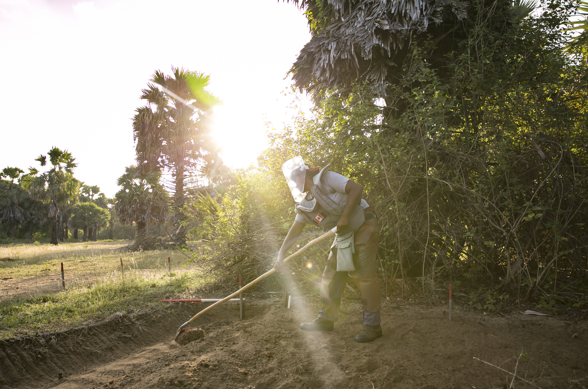 A female de-miner works to clear mines in Muhamalai, one of the biggest minefields in the world