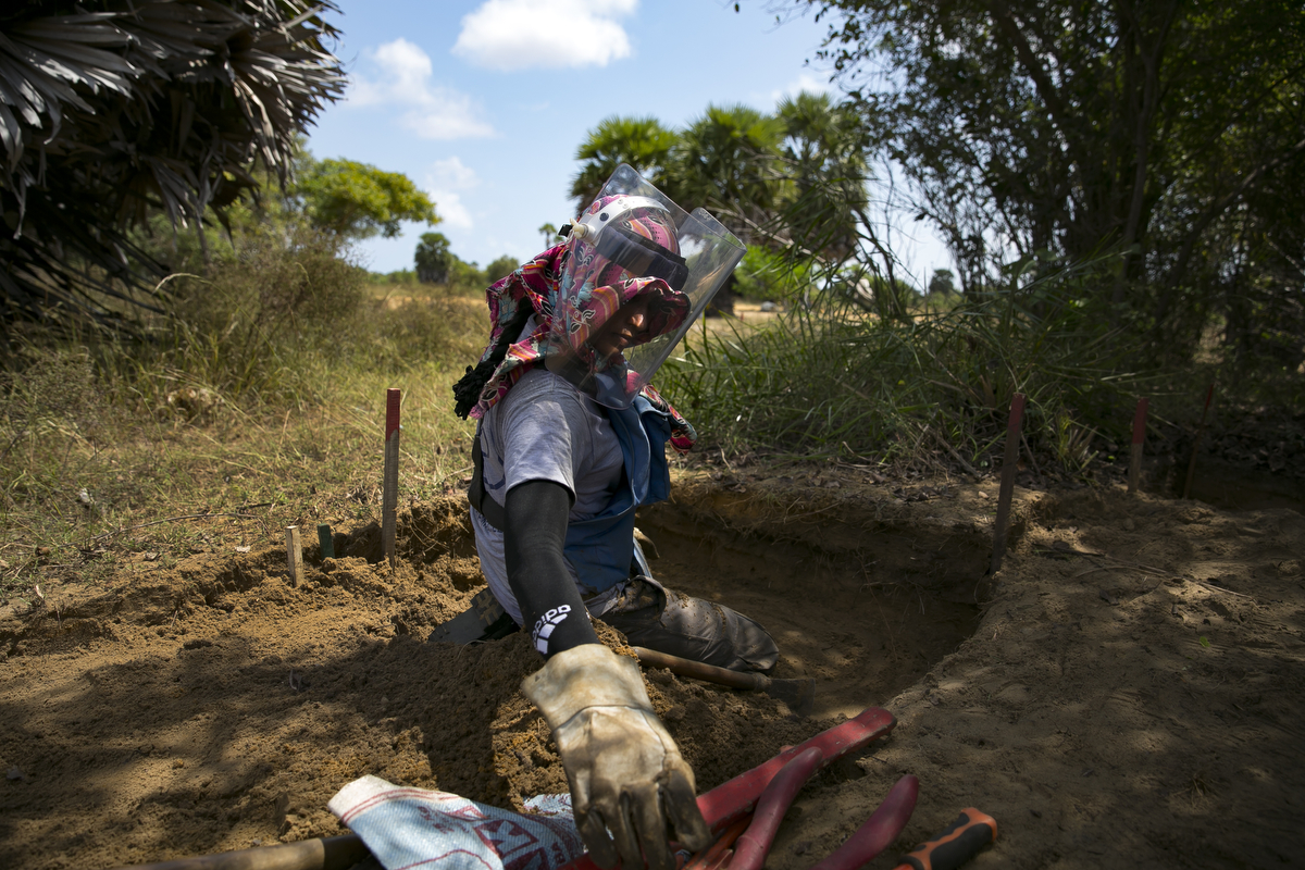 A female de-miner works to clear mines in Muhamalai, one of the biggest minefields in the world,