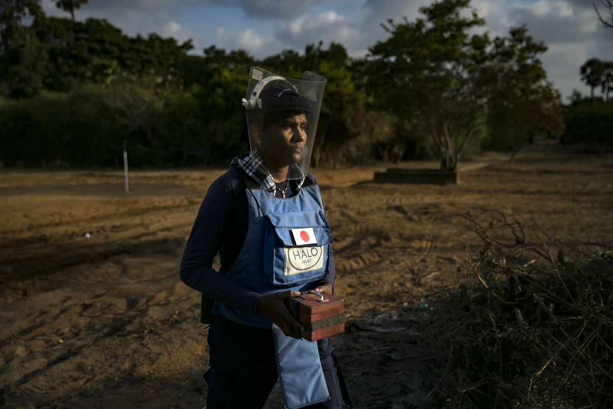 A female de-miner carries a live mine to a safe box