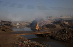 A man crosses a bridge over a polluted canal which empties out into the Buriganga river.