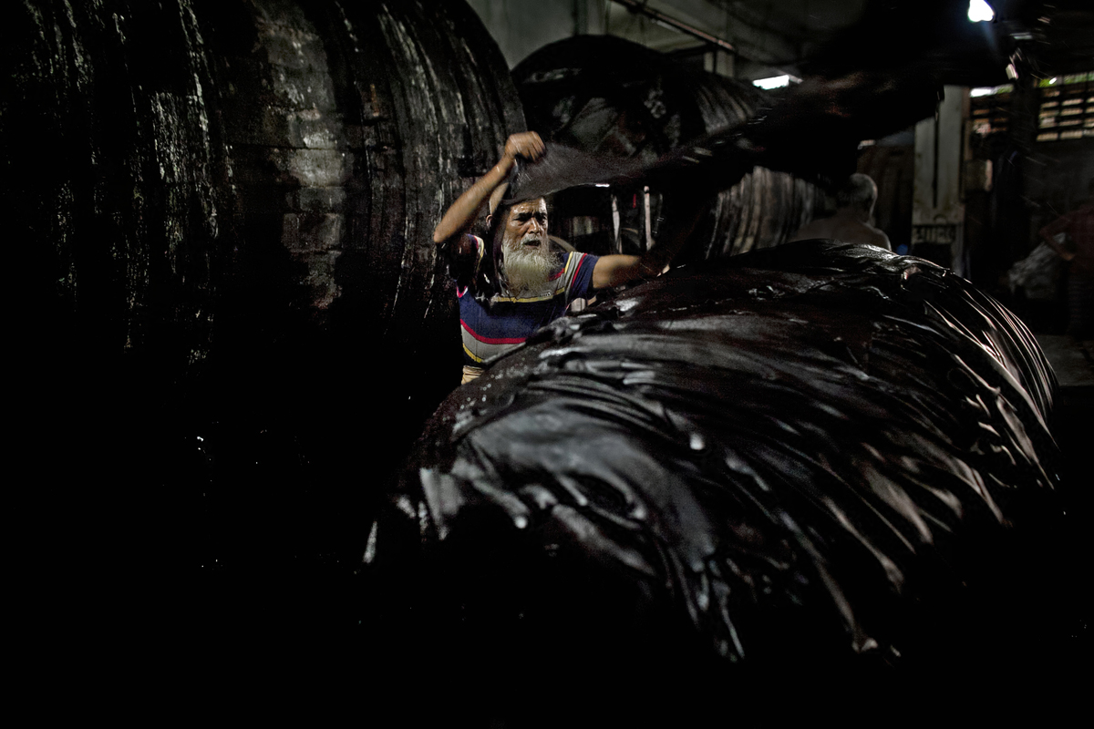 63 year old Abu Talib unloads leather hides from a vat of chemical mixture in a tannery, the Phoenix Leather Complex. Talib has been working in the tannery for 9 years. He says that sometimes he gets itchy rashes on his skin and has breathing problems if the mixture is especially acidic. He earns anywhere from 8,000 to 9,000 (about $102 to $115) taka a month.