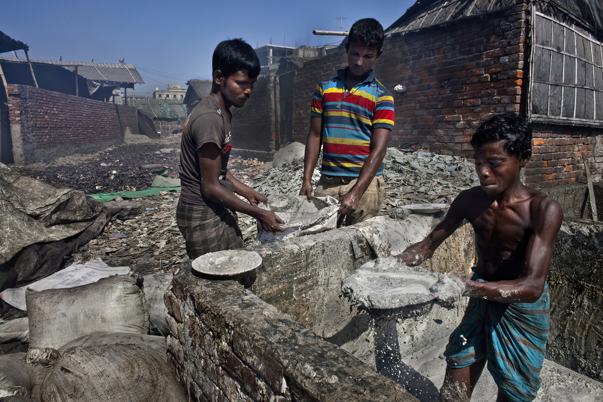 (L-R) 24 year old Mohammad Alamgir, 16 year old Mohammad Hasan, and 13 year old Biplop Mohammad work bagging animal fat that will be turned into soap.