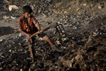 10 year old Mohammad Kadirul Islam sorts through animal waste looking for horns. His family pulled him from school one year ago and sent him to Dhaka to start making money after his father was diagnosed with cancer. The 2,000 (about $25) taka he makes a month is sent back home to his mother. Kadirul says that he wanted to stay in school and study to be a teacher. Even though his hands often get damaged with the work he does his employer won't replace the old pair of gloves he wore through.