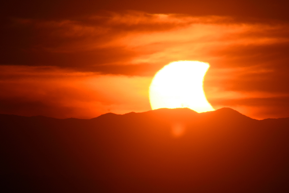 A partial solar eclipse is seen setting behind the Blue Ridge Mountains from a vantage point on Candler\'s Mountain Thursday evening, Oct. 23, 2014  in Lynchburg, Va.