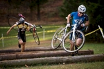 Owen Nielsen, right, and Baird Sills, left, dismount and jump over obstacles while running uphill carrying their bikes during the Dire Wolf Cross cyclocross race at Falling Creek Park in Bedford this month.