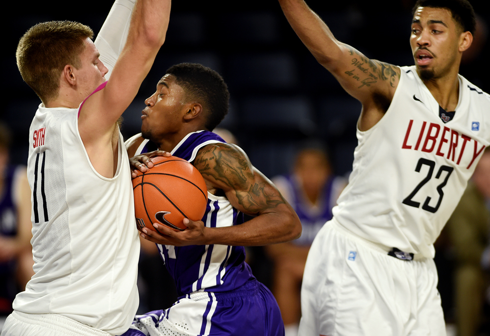 Liberty\'s Andrew Smith (11) is fouled by Furman\'s Stephen Croone (44) late in the second half of LU\'s 66-52 win during a NCAA men\'s baskeball game Monday night at the Vines Center in Lynchburg, Va.
