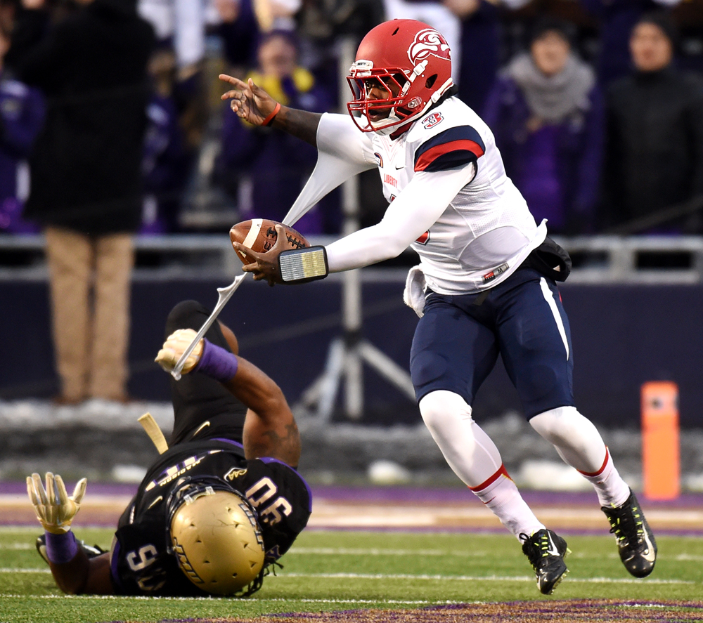 JMU\'s Alex Mosley (90) keeps a hand on LU\'s Stephon Masha (3) during the first half of an NCAA FCS Playoff game between Liberty University and JMU in Harrisonburg, Va.