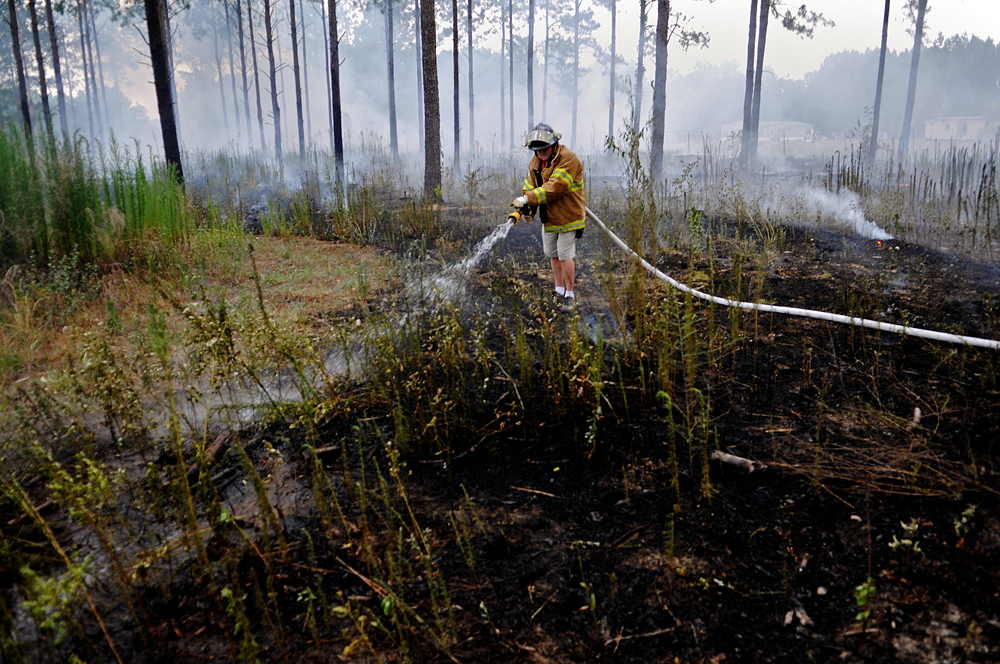 A volunteer firefighter sprays water on a brush fire in Houston County.