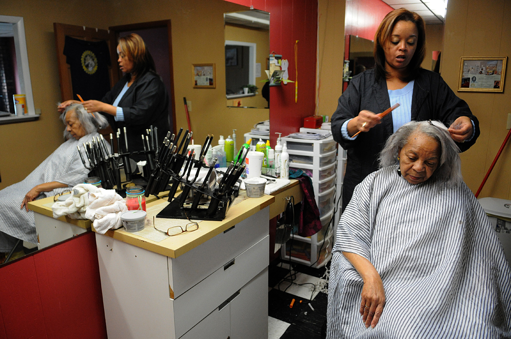 A woman receives a haircut at a barber shop in downtown Ozark, Ala.