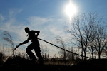 A volunteer firefighter is silhouetted by the sun as he sprays water on a brush fire near Columbia, Ala.