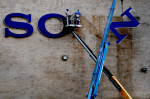 Workers use a crane to remove letters from the logo on the side of the former Sony plant in Dothan, Ala. February 10, 2011.