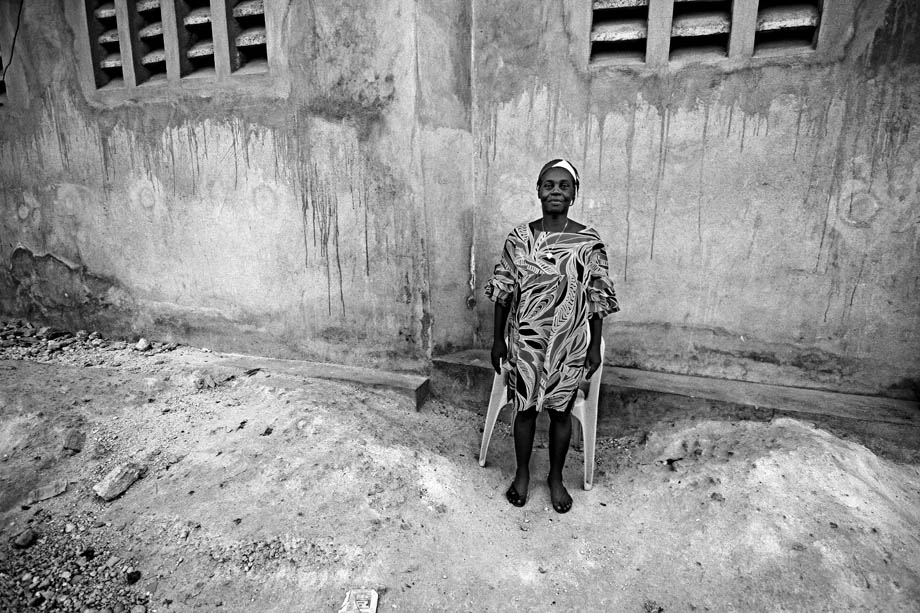 A woman, who asked not to be identified, stands for a photograph outside her home in Carrefour, Haiti.