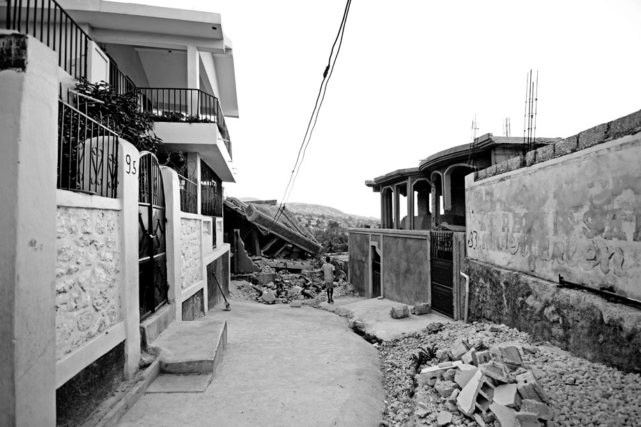 A young boy stands at the end of a road in Carrefour, Haiti in early February 2010. The earthquake left houses on one side of this particular street with virtually no damage, and on the other, homes were completely destroyed.
