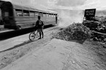 In the weeks following the January 12, 2010 earthquake, many Haitians attempted to return to as normal a life as they could. In this photo, a man waits for a bus to pass before riding his bicycle down Haiti's debris-strewn Route Nationale 1.