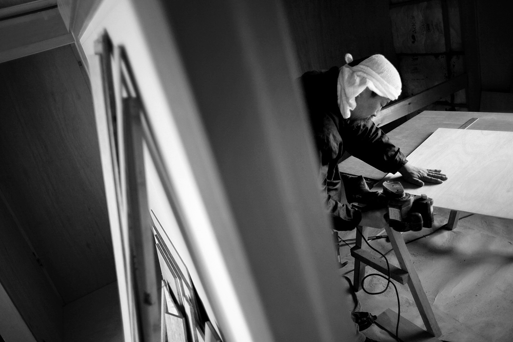 Staff member Jun Amano makes a cut to a piece of wood during the reconstruction of the Watanabe family's home.