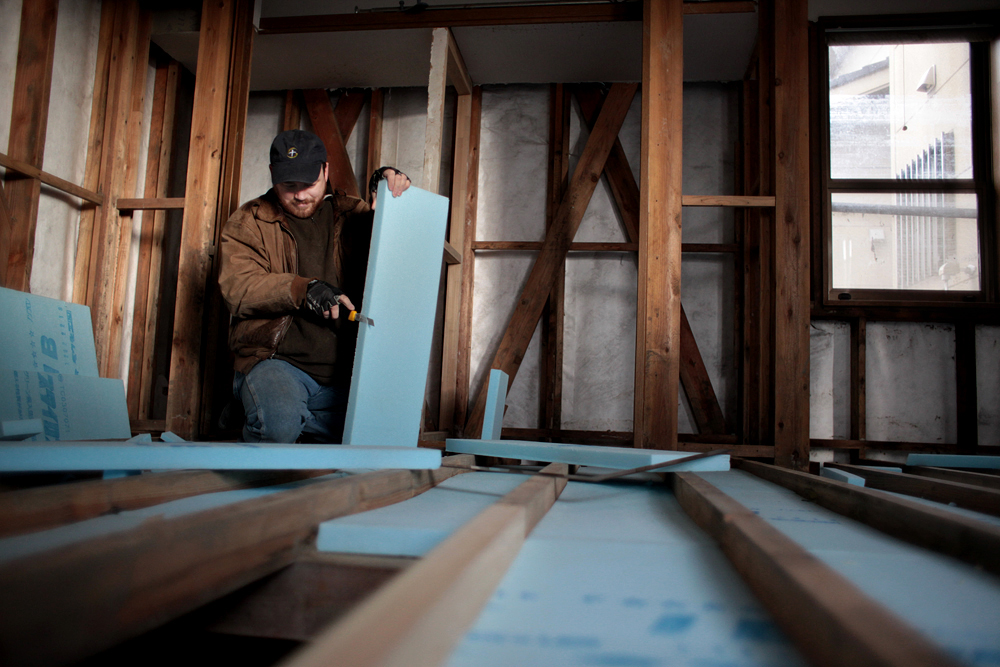 Carpenter Rob Sherwood cuts insulation for the floor inside the Matsunaga family home.