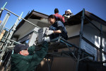 Volunteers with Samaritan's Purse help Japanese carpenters remove roof tiles from a home in early March.