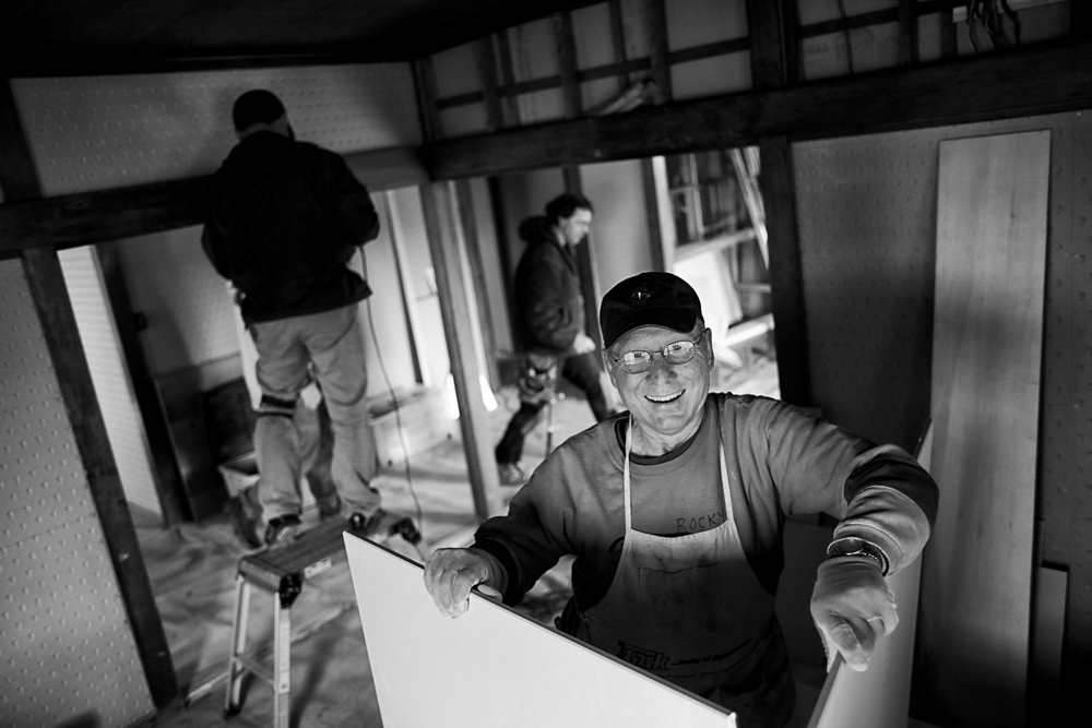 A Samaritan's Purse volunteer smiles as he works with a crew on a tsunami-damaged home.