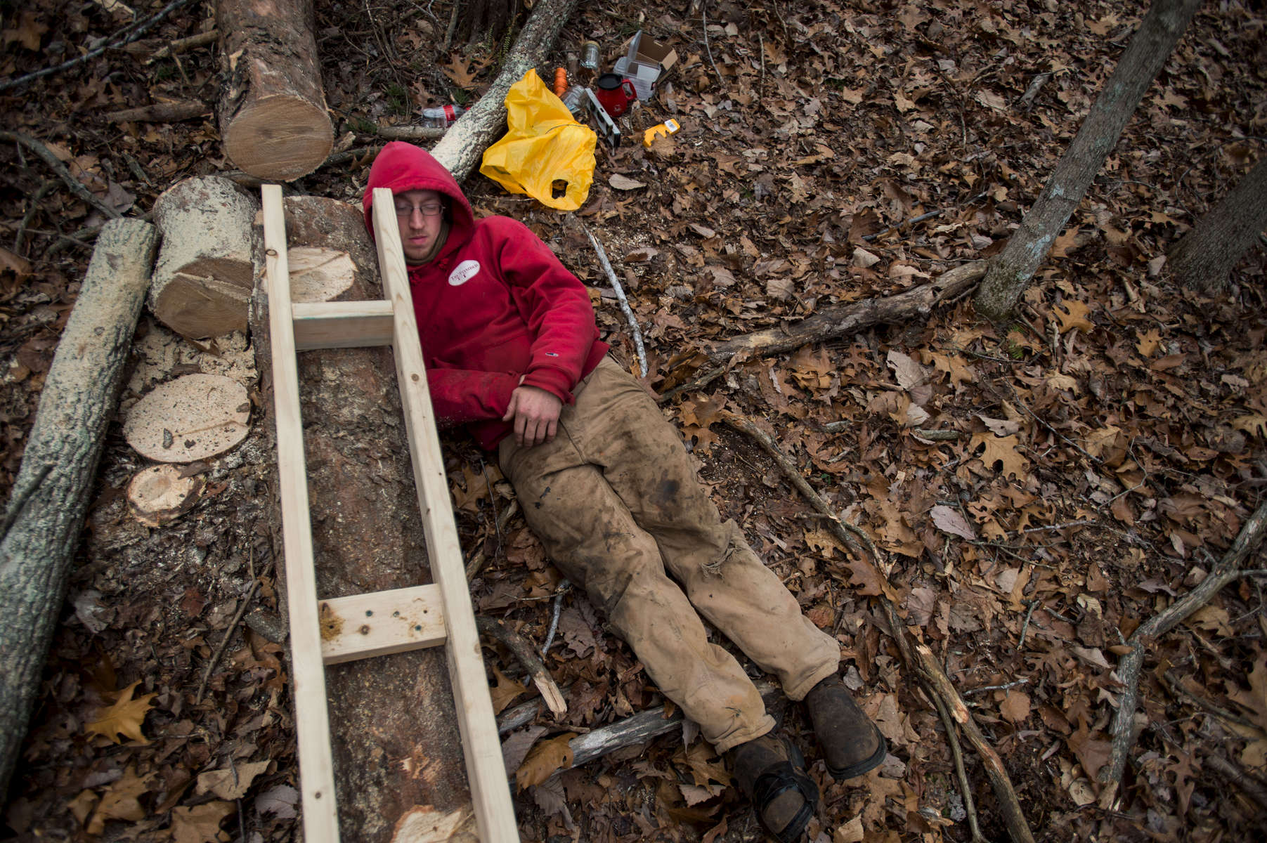 Isaac Schumacher looks for curves in a tree felled for lumber on a friend's property in Appomattox.