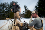 In late February, after a severe winter storm left nearly a foot of snow on the ground, Robert Schumacher, right, and his son Isaac, worked to cut the batteau's cap rails out of a nearly 50-foot piece of lumber milled from one of the two trees cut down by Isaac earlier in the month.