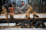 Isaac Schumacher and his father, Robert Schumacher, work together in late February to cut the Lizzie's cap rails into shape.