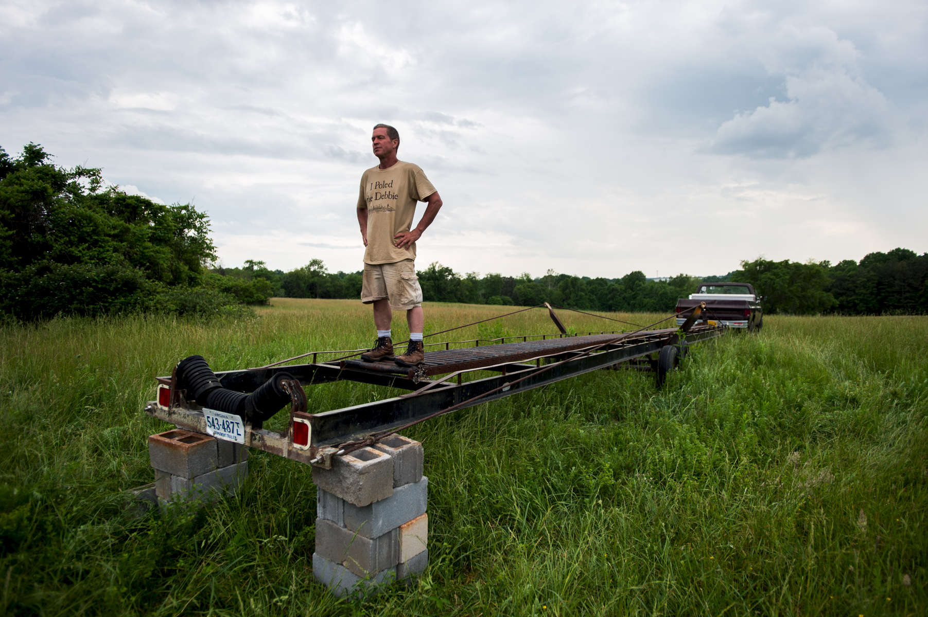 Robert Schumacher pauses for a moment as he stands on a trailer during a cook out for members of the batteau community in and around Lynchburg. Around 50 people came together to flip the Lizzie Langley over and load her onto a trailer for transportation to the James River.
