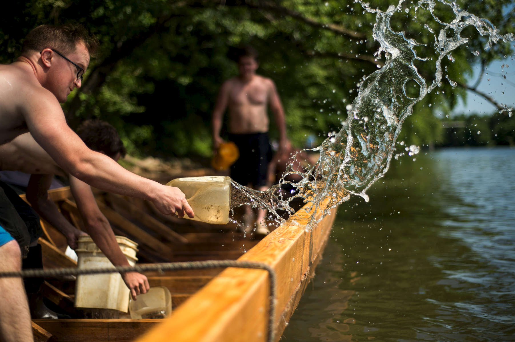 Dylan Schumacher bails water out the batteau Lizzie Langley in late May on the James River.