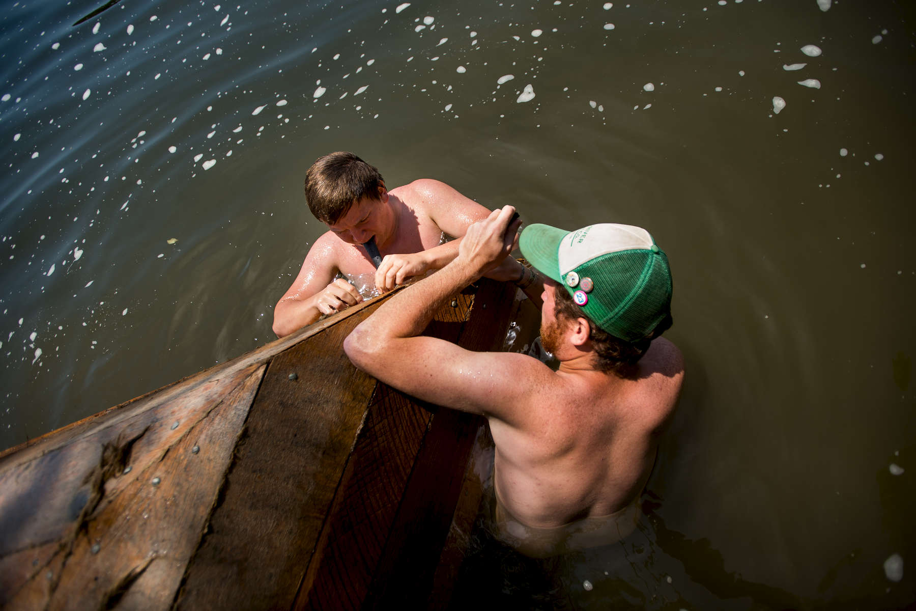 Nathan Shabestar and Dan Tucker fill small holes in the batteau's hull with oakum, a product made of hemp and petroleum that acts as a caulking and water sealant for the boat.