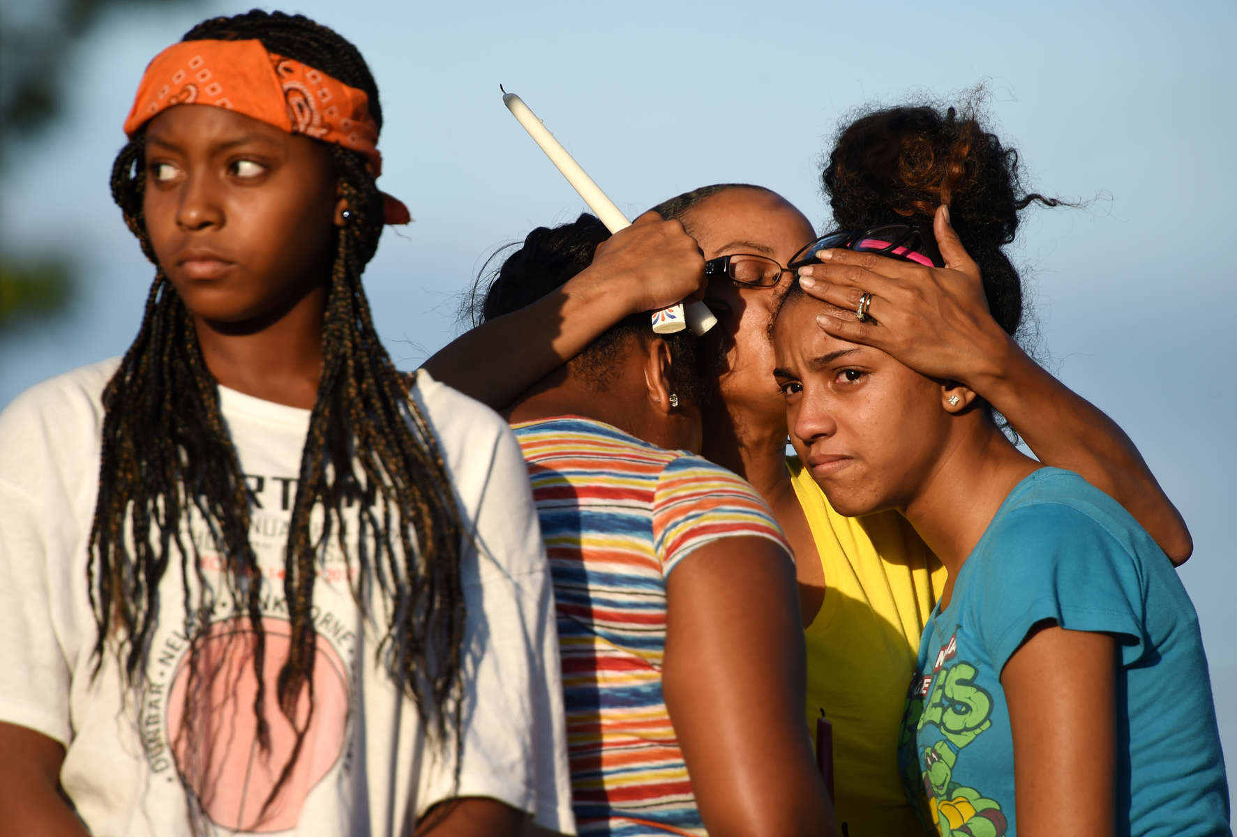 Relatives of Lawrence Maliek Giusto console each other during a vigil Monday evening in Lynchburg. Giusto was killed Sunday morning in a drive-by shooting on Shaffer Street. (Photo by by Max Oden / The News & Advance)
