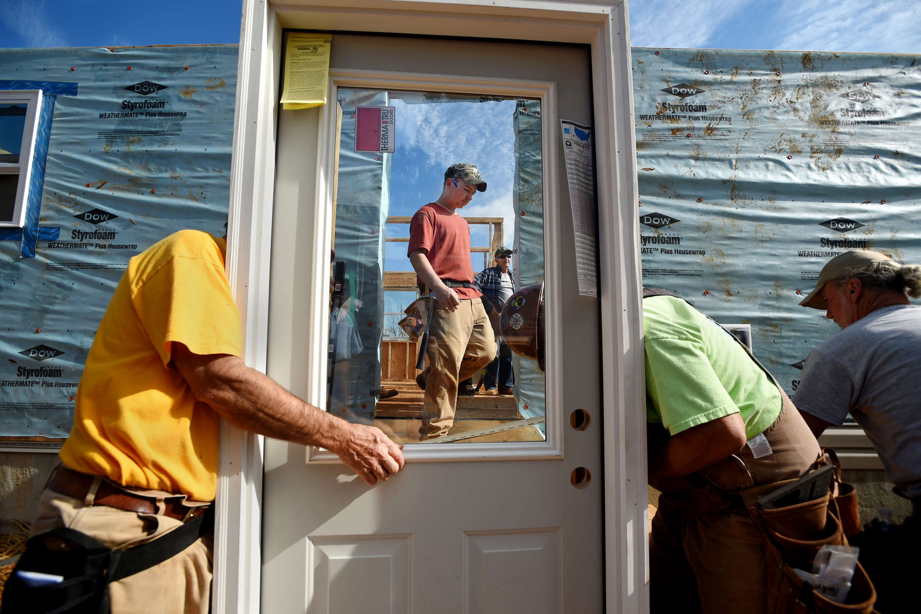 Habitat for Humanity volunteer Jonathan Browning, center, of Amherst, is seen through the window of a door being installed in one of two homes volunteers worked to construct Saturday during a Habitat for Humanity 'Blitz Build' in Altavista.  (Photo by Max Oden/The News & Advance)