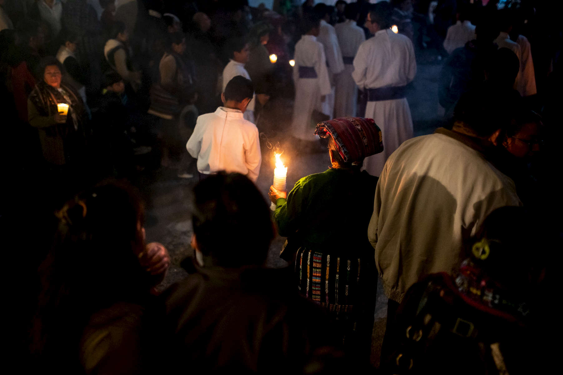 A Mayan woman holds a candle as she walks with the procession on March 29th, 2019 during Lent in Panajachel, Guatemala.