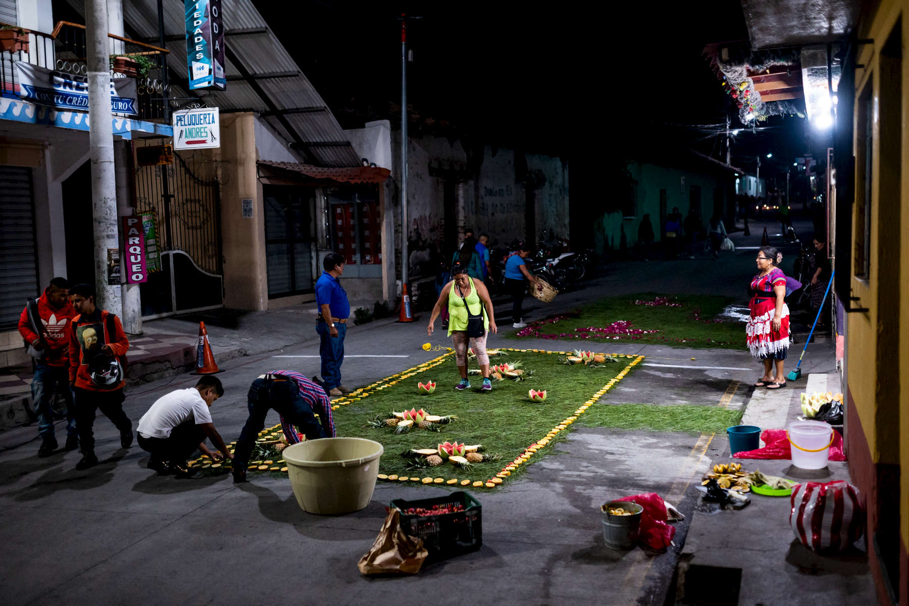 Residents of Panajachel make a carpet out of pine needles and fruit for the procession to pass over during it's route back to the church on Maundy Thursday.