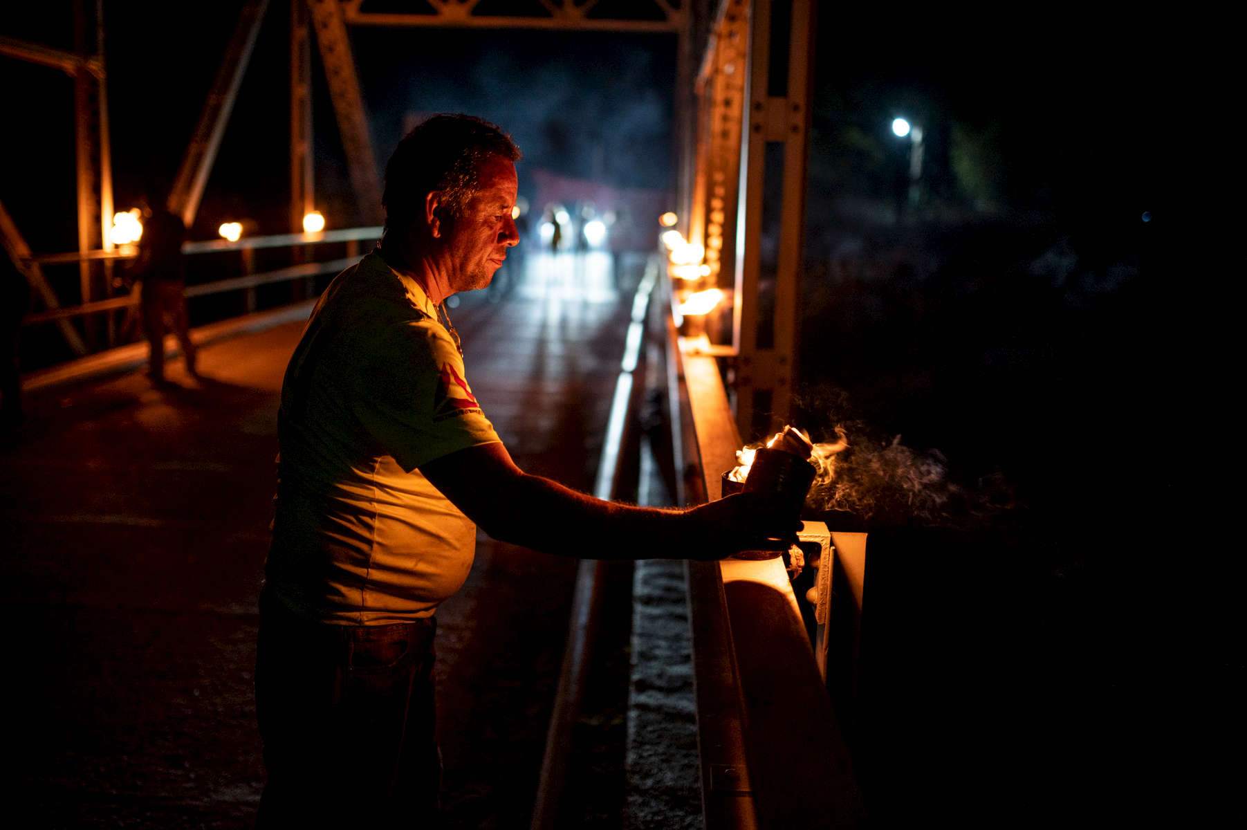 A man lights a candle to illuminate the Ubico bridge outside of Panajachel during the Maundy Thursday procession in Panajachel, Guatemala.