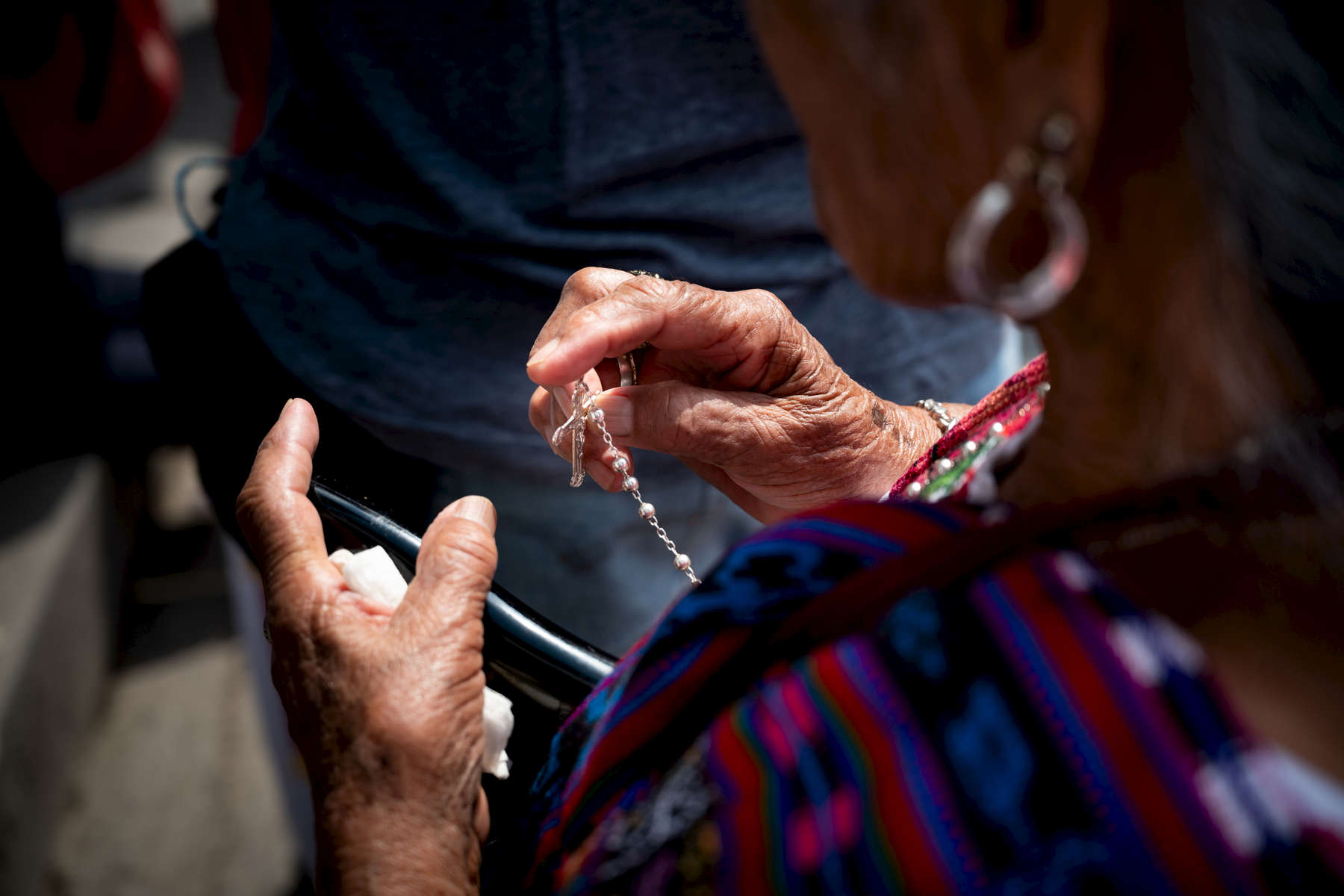 An indigenous Mayan woman clutches her rosary at the first Station of the Cross on Good Friday in Panajachel, Guatemala.