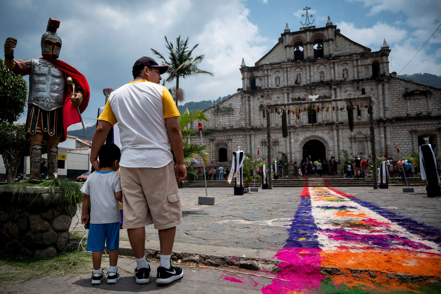 A father and son stop by the the Iglesia San Francisco in Panajachel before the final procession of Good Friday leaves.