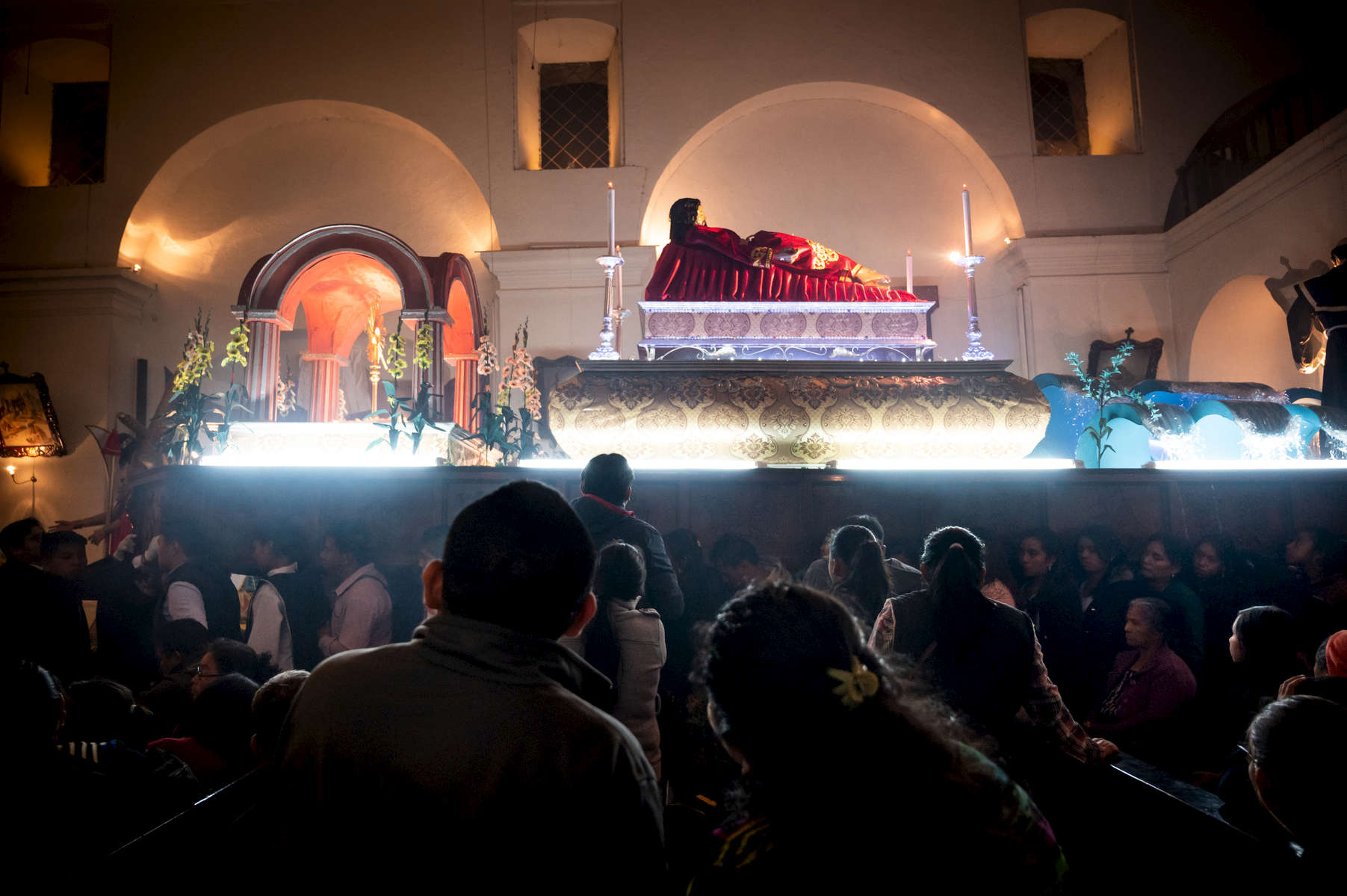 Catholic worshippers watch as the anda with the body of Jesus Christ is brought into the church on April 20, 2019.