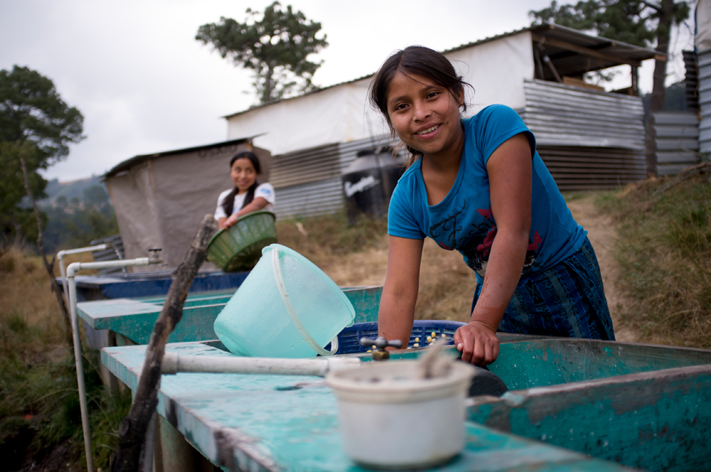 A young woman from the village of Chutinamit smiles as she washes corn for tortillas. The village was relocated to its current location after Tropical Storm Agatha in 2010. The residents are still living in transitional housing three years later.