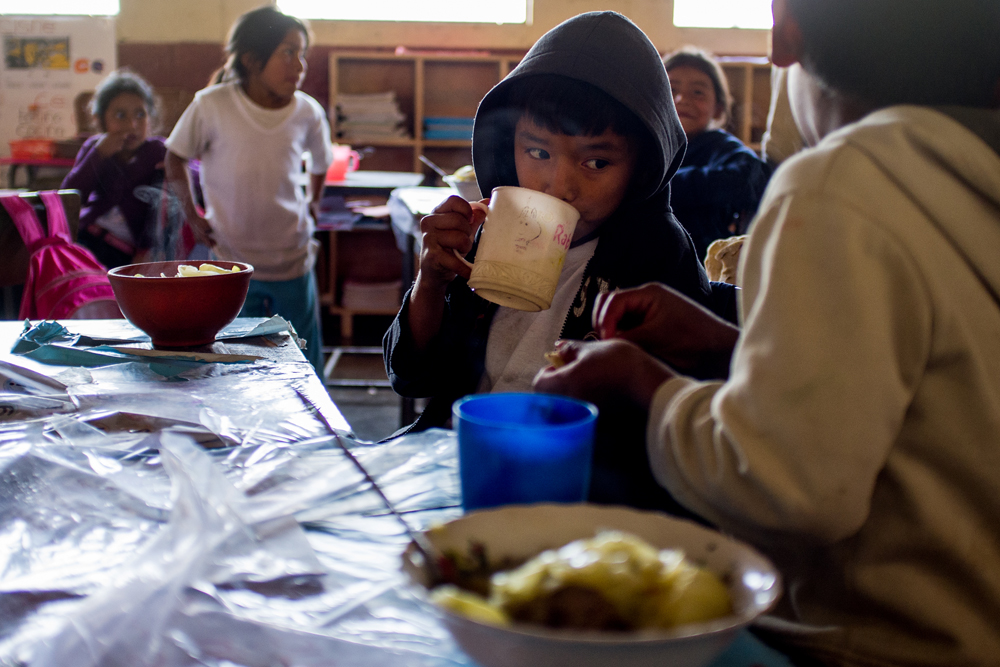 A young boy enjoys a cup of atole during the first day of operation of the Mission Guatemala-run feeding program in Xepec. Mission Guatemala provideds over sixty students with a healthy meal each school day in Xepec.