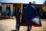 Dressed in full luchador regailia, the principal of an elementary school in the village of Nueva Esperanza walks with a student towards a classroom.
