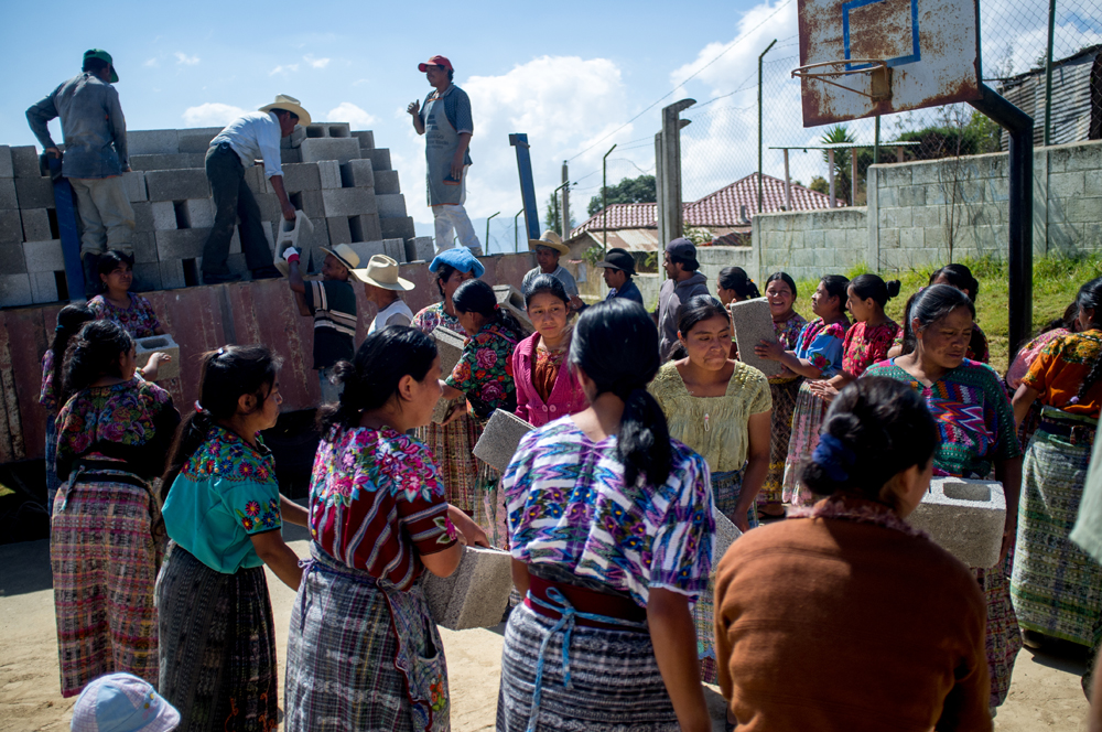 Dozens of residents of the village of Caliaj work together to unload construction materials from a flatbed truck.