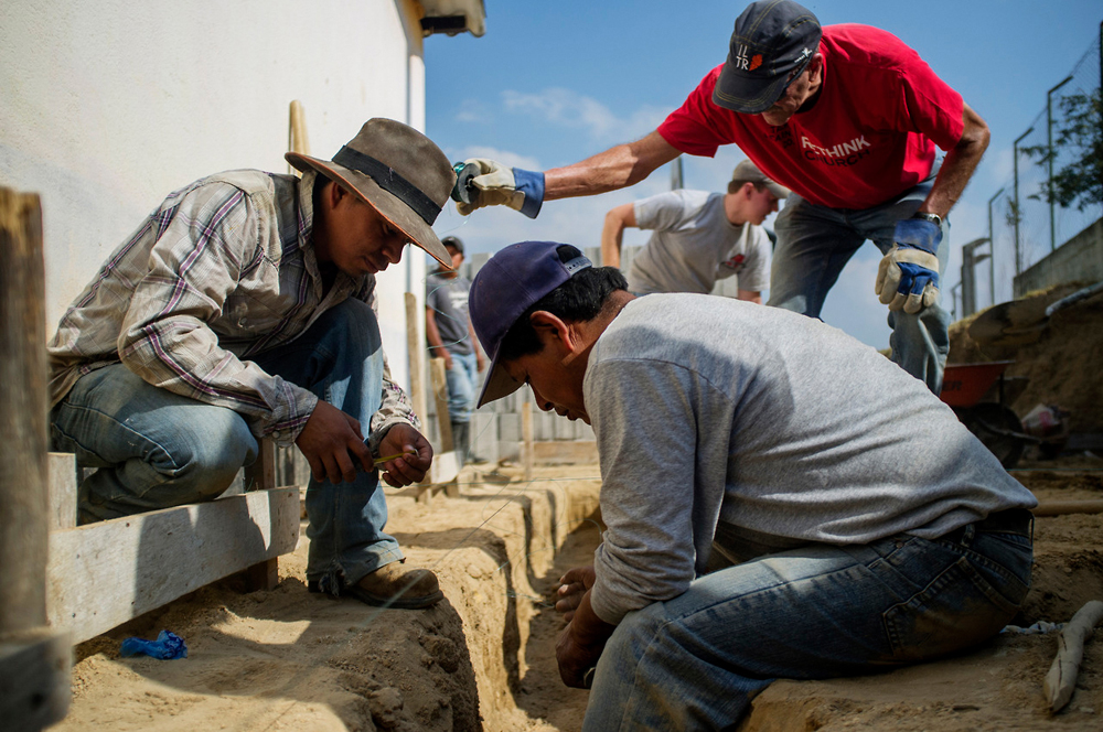 Mission Guatemala construction foreman Elias Coroxon, left, works with volunteers to prepare the footing for a building that will house seven flush toilets and a shower at the elementary school in the village of Caliaj.