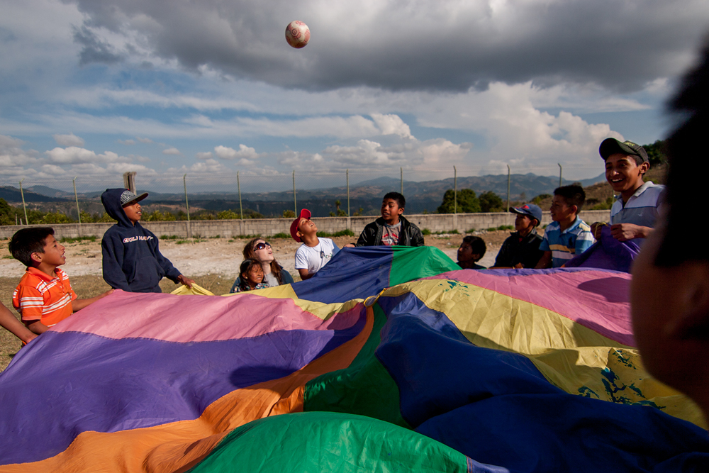 A mission team volunteer plays with children from an elementary school in the village of Caliaj, Guatemala.