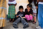 Henry, 8, a student at the school in the village of Caliaj, reads the book {quote}Leyendas de Guatemala{quote} (Legends of Guatemala) to a classmate in May 2013.