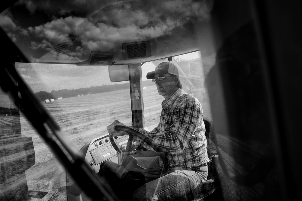 Clouds are reflected in the windshield of Dewayne Womack's tractor as he harvests peanuts from a field in Jackson County, Fla., on Oct. 26. Womack, an employee of Floyd Farms, has been working with peanuts for 30 years.