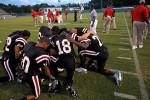 Dothan High School football players huddle in prayer as rescue workers attempt to revive referee James Parrish on August 28, 2009. Parrish died after suffering a heart attack during the game.